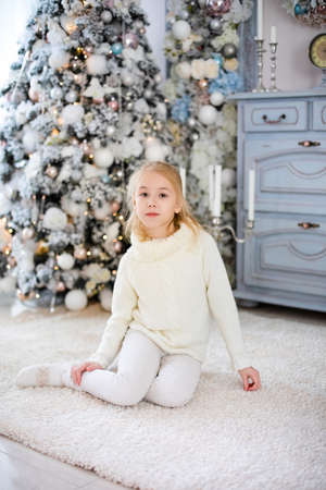 Christmas portrait of happy blonde child girl in white sweater siting on the floor near the Christmas tree. New Year Holidays.
