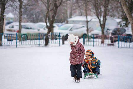 Boy and girl sledding in the snowy yard. Winter background. Banco de Imagens