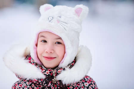 Smiling girl with white fur hat like a cat. Winter snowy background.