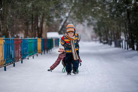 Boy and girl sledding in the snowy yard under the trees. Winter background.