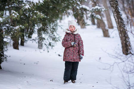 Smiling girl with white fur hat like a cat. Winter snowy background and gteen tree. Banco de Imagens