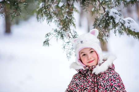 Portrait of smiling girl with white fur hat like a cat. Winter snowy background and gteen trees.