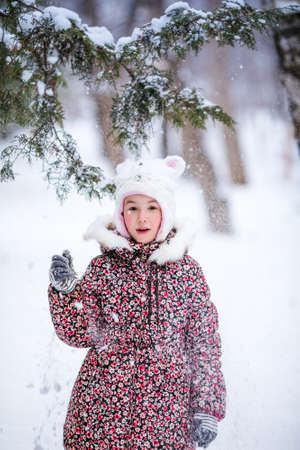 Smiling girl with white fur hat like a cat playing with snow. Winter snowy background and gteen trees. Banco de Imagens