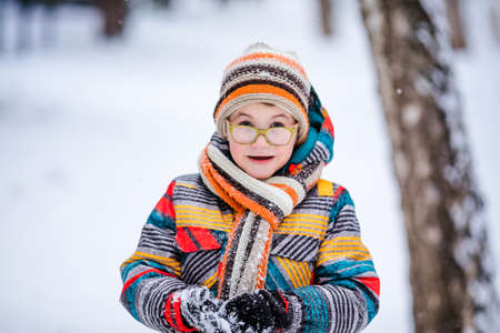 Smiling boy with green big glasses, knitting hat and scarf. Winter snowy background.