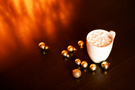 White mug with hot chocolate and marshmallows on the dark brown table and background with golden bokeh. Christmas holiday concept, free space for text.