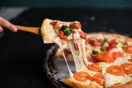 Delicious cheese stringy slice lifted of full supreme pizza