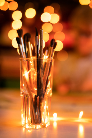 Glass with old artist brashes. Background with warm yellow bokeh. Christmas and New Year theme.