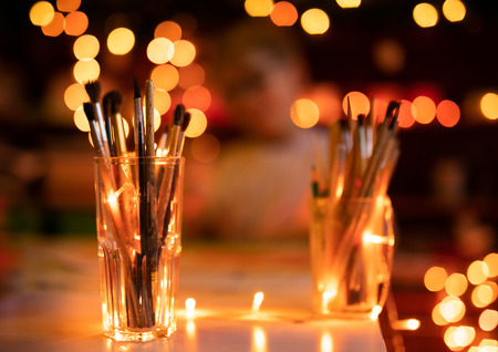 Glass with old artist brashes. Background with warm yellow bokeh. Christmas and New Year theme