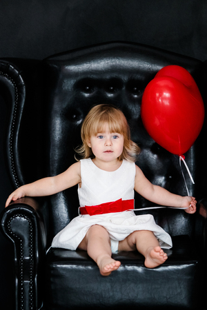 Little blonde girl in white dress with red ribbon sitting on the armchair with red heart balloon on the St. Valentine's day. Black background.