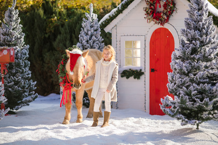 Cute blonde girl and adorable pony with wreath near the small house and snow-covered trees. New Year and Christmas time.