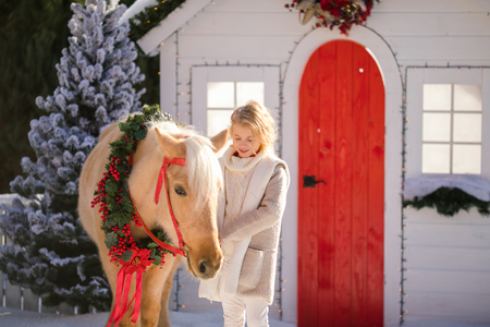 Close-up nice blonde curly kid and adorable pony with festive wreath near the small wooden house and snow-covered trees. New Year and Christmas time.