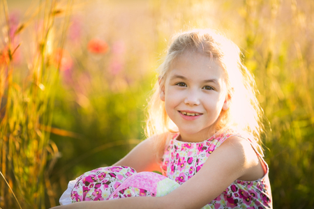 Das Porträt von blonden Mädchensitzen auf dem Blütengebiet n den Sonnenuntergang.