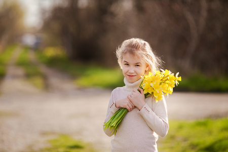 cute blonde happy little girl with yellow daffodils in the spring country.