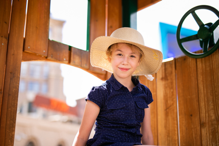 Blonde girl in the hat in the wooden house on the children playground.