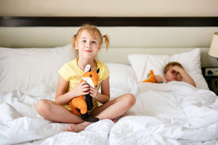 Blonde girl in yellow t-short and with toy orange fox in the white bed.