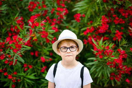 Ginger boy in the straw hat and big glasses near the green bush with red flowers in the summer park.