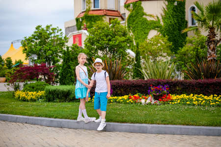 Blonde girl in white and blue dress and ginger boy in the hat and big glasses in the summer park with decorations. Foto de archivo