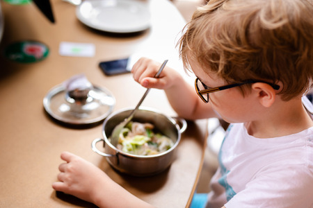 Blonde boy with big glasses having lunch in the restaurant.