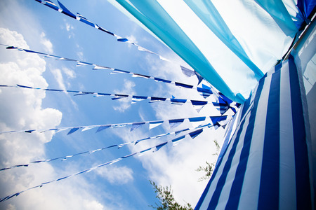 estival flag line with blue sky in background. flag background hanging on blue sky for fun fiesta party event, summer holiday farm feast celebration, carnival. Stock Photo