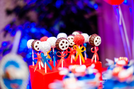 Candy bar on boy's birthday party with a lot of different candies, popcorn, beverages and big cake standing on a barrel. Decorated in bright colors. Hot wheels, cars or racing theme. Summer, outdoor. 写真素材