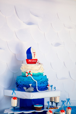 Huge blue birthday cake with sweet whale and lifebuoy and funny ship on the top. Summer season delicious on the party. Sea time theme on the candy bar. Stock Photo