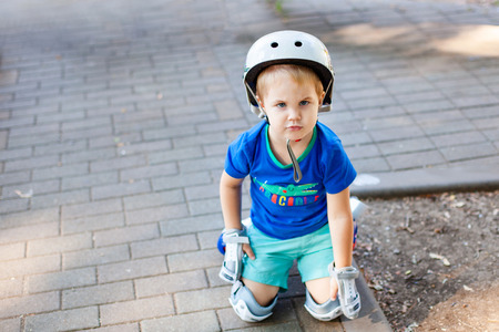 Little blonde boy 3 years old in white sport helmet and blue t-shirt riding on the roller-slates in the summer green park. Special problems with kid's eyes. Myopie, astigmatism, cross-eyed. Standard-Bild