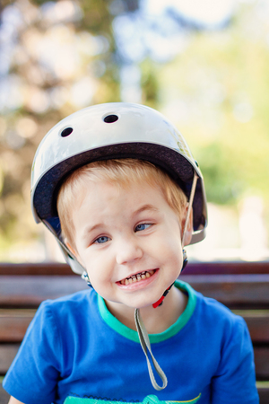 Little blonde boy 3 years old in white sport helmet and blue t-shirt outside. Special problems with kid's eyes. Myopie, astigmatism, cross-eyed. Stockfoto