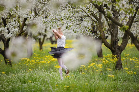 Blonde girl in gray skirt and white shirt playing and running in the cherry blossom garden.