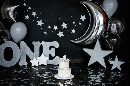 Torta bianca primo compleanno con stelle e candelina per neonato e decorazioni per schiacciata Grandi lettere d'argento UNO, stelle d'argento e palloncini diversi.