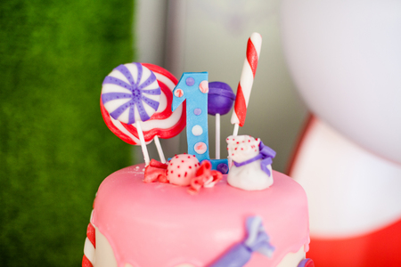 Birthday pink cake with candies and lolly-pops, different details Stock Photo
