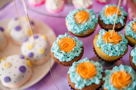 Verjaardagsfeestje concept. Tafel voor kinderen met cupcakes met blauw en oranje blad en decoritems in felroze en blauwe kleuren Stockfoto