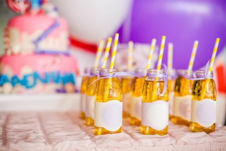 Concept de fête d'anniversaire, barre chocolatée pour enfants. Beaucoup de bouteilles de jus de pomme, pailles blanches et jaunes, gros gâteau rose et ballons blancs et violets sur fond Banque d'images