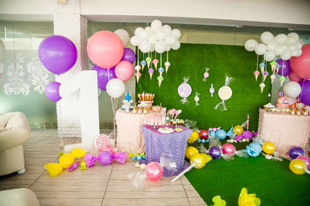 Birthday party concept, decorations for sweet party. Huge number one, table with sweets and desserts, cloud from balloons and ice-creams, a lot of colored balloons and big candy toys