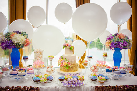 Candy bar on golden wedding party with a lot of different candies, cupcakes, souffle and cakes. Decorated in brown and purple colors, nature and eco theme, indoor.