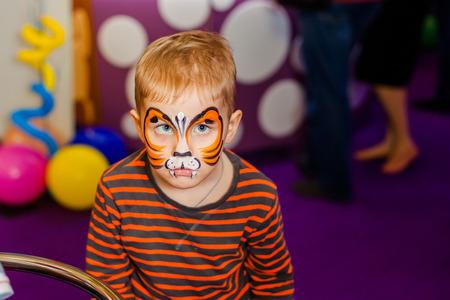 Animateur d'enfant, la main de l'artiste dessine la peinture faciale pour le petit garçon. Enfant avec la peinture de visage drôle. Le peintre fait un tigre orange sur le visage du garçon. Vacances pour enfants, événement, fête d'anniversaire, animation.