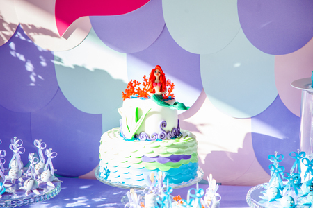 Sea time mermaid theme on the party's candy bar with purple background. Birthday party for girls, teens.