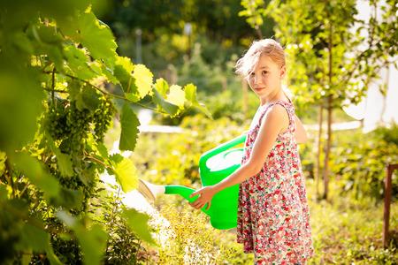 Entzückendes blondes Mädchen im großen Strohhut, der im Garten arbeitet. Teenager-Kind, das auf dem Bauernhof hilft. Standard-Bild