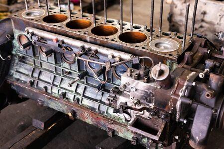 Mechanic repairs old motor of truck in a car repair station. Disassemble engine block vehicle. Motor capital repair. Car service concept.