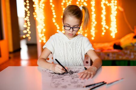 Adorable litle girl is writting a letter to Santa Klaus sitting on the table.