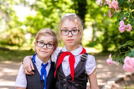 A schoolgirl in a white blouse with a red tie, with a bow and her little brother with blue tie and glasse in the class. Back to school concept.