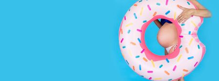 Happy pregnant women in swimsuit with swimming ring donut on a colored blue background. Stock Photo