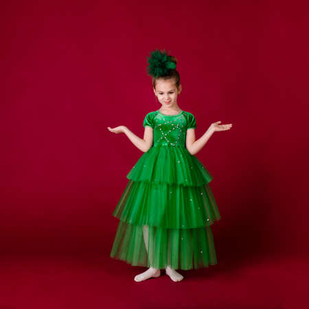 Beautiful little girl princess dancing in luxury green dress isolated on red background. Carnival party with costumes.