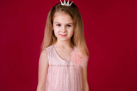 Beautiful little girl princess dancing in luxury pink and silver dress isolated on red background. Funny face, different emotions.