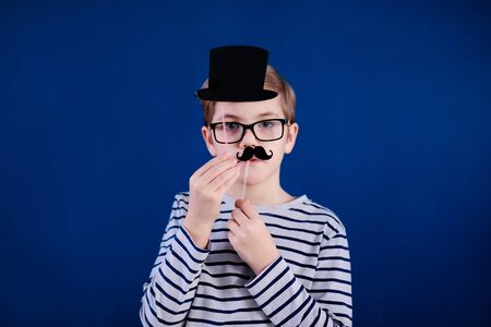 Birthday party and young boy with glasses in hats and props on blue background.