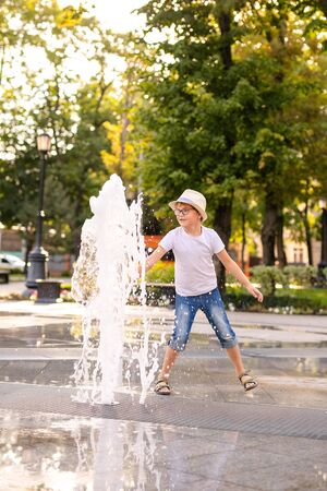 Excited boy in hat and glasses running between water flow in city summer park. Child activity concept.