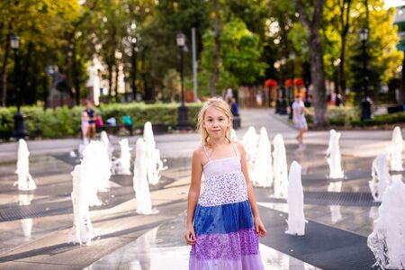 Blonde happy child girl in long purple dress running between water flow in city summer park. Child activity concept.