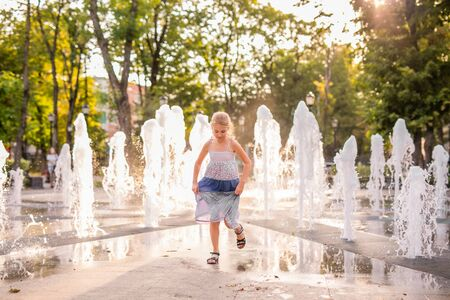 Blonde happy child girl in long purple dress running between water flow in city summer park. Child activity concept, Modern warm toned.
