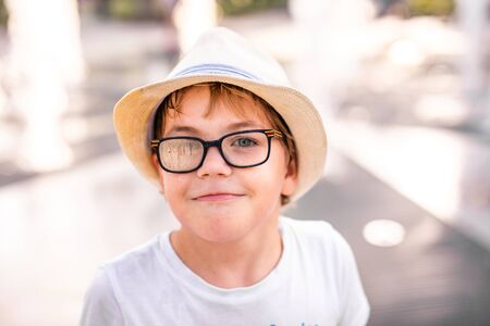 Little caucasian boy in hat and big glasses playing and having fun with water in fountain in the sunny summer park