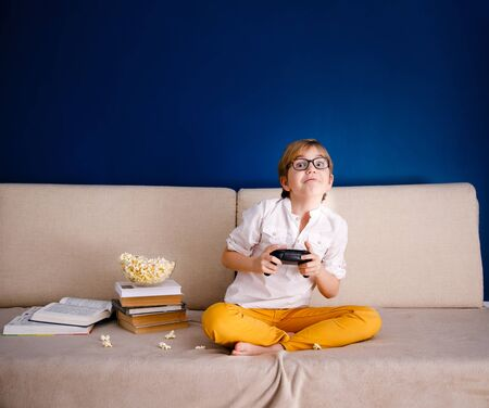 Blonde 9-year-old boy in white T-shirt and big glasses sitting on the couch, eating pop corn and playing at home with a gamepad during his online lesson at home, social distance during quarantine, self-isolation, online education concept, home schooler