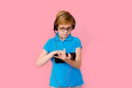 Boy studying homework with tablet pc and earphones during his online lesson at home, social distance during quarantine. Pink background with free space for text.
